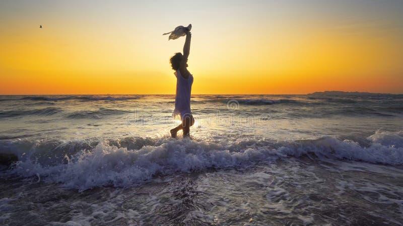 Γυναίκα ελευθερίας και ευτυχίας χαμόγελου στην παραλία στο ηλιοβασίλεμα στοκ φωτογραφία με δικαίωμα ελεύθερης χρήσης