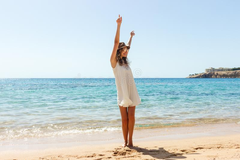 Γυναίκα ελευθερίας στην ελεύθερη ευδαιμονία ευτυχίας στην παραλία Χαμογελώντας ευτυχές κορίτσι στο άσπρο θερινό φόρεμα στις διακο στοκ εικόνες
