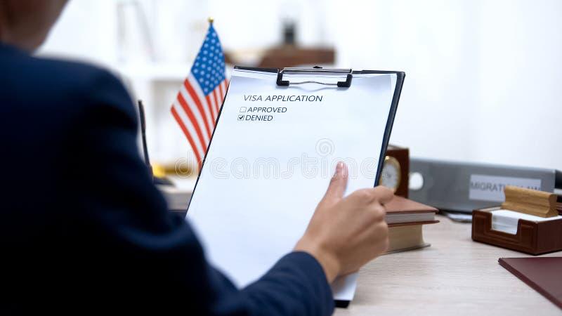 Γυναίκα επιθεωρητής μετανάστευσης αρνείται αίτηση βίζα, τραπέζι με αμερικανική σημαία στοκ εικόνες