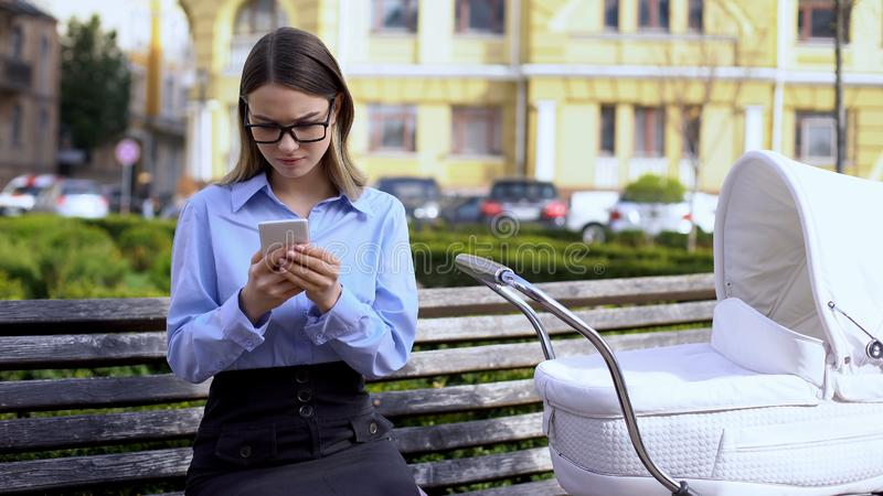 Γυναίκα επιχειρηματίας που στέλνει email στο smartphone αγνοώντας το μωρό στην άμαξα, την καριέρα της στοκ φωτογραφία με δικαίωμα ελεύθερης χρήσης