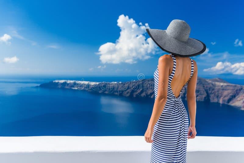 Γυναίκα διακοπών ταξιδιού πολυτέλειας που εξετάζει Santorini στοκ φωτογραφίες