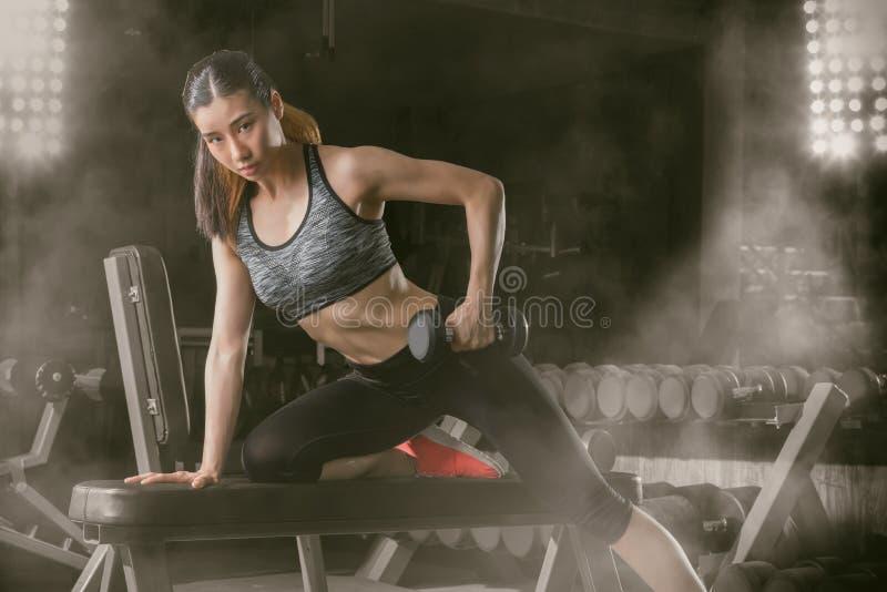 Γυναίκα ικανότητας, ασιατική αθλητική γυναίκα που αντλεί επάνω τους μυς με τους αλτήρες στοκ εικόνες