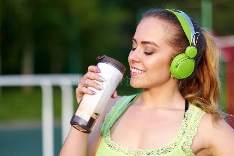 Γυναίκα ικανότητας με το πόσιμο νερό ακουστικών στο χώρο αθλήσεων workout στοκ εικόνα με δικαίωμα ελεύθερης χρήσης
