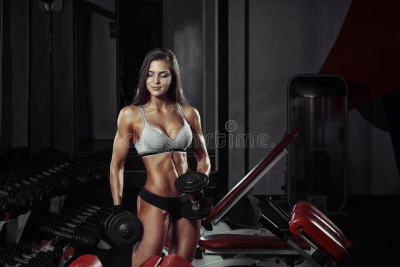 Γυναίκα ικανότητας που κάνει μια ικανότητα workout με τους αλτήρες στη γυμναστική στοκ φωτογραφία