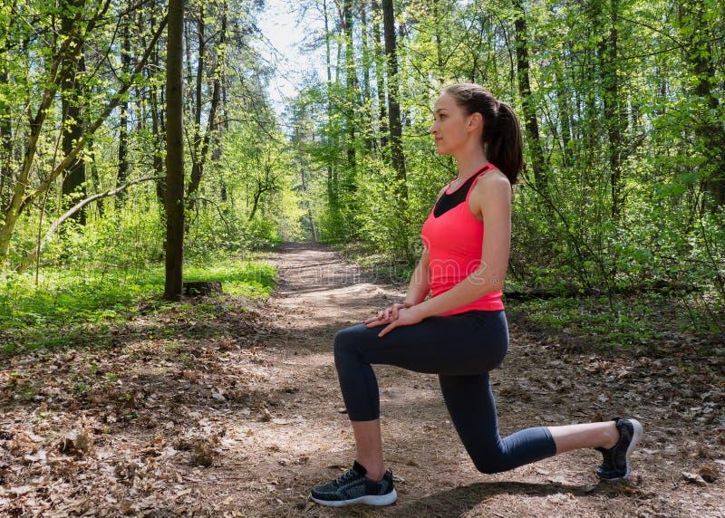 Γυναίκα ικανότητας που κάνει μπροστινό lunge πριν από το τρέξιμο στο θερινό δάσος στοκ φωτογραφίες