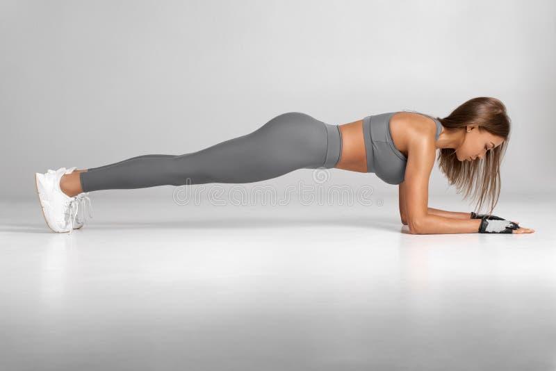 Γυναίκα ικανότητας που κάνει τη planking άσκηση, workout Λεπτή αθλητική κατάρτιση κοριτσιών, που απομονώνεται στο γκρίζο υπόβαθρο στοκ εικόνες