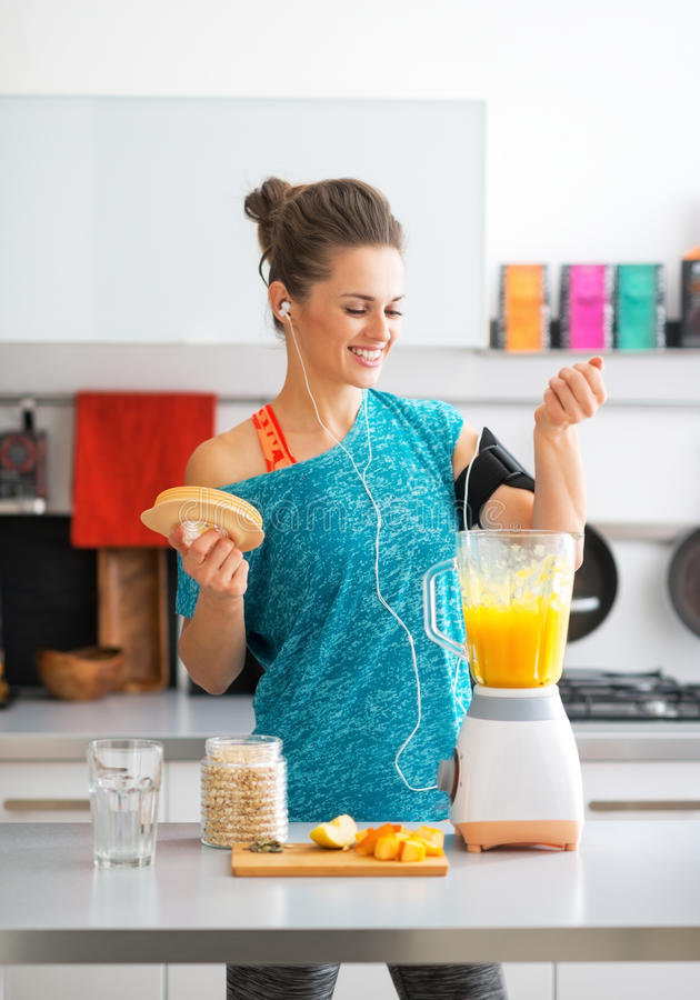 Γυναίκα ικανότητας που κάνει το καταφερτζή κολοκύθας στην κουζίνα στοκ φωτογραφίες