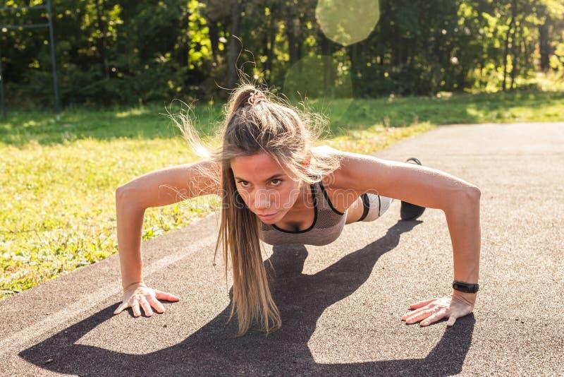 Γυναίκα ικανότητας που κάνει το ώθηση-UPS κατά τη διάρκεια του υπαίθριου σταυρού που εκπαιδεύει workout Όμορφη νέα και κατάλληλη  στοκ εικόνα με δικαίωμα ελεύθερης χρήσης