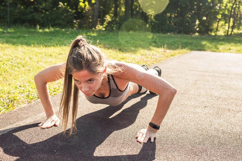 Γυναίκα ικανότητας που κάνει το ώθηση-UPS κατά τη διάρκεια του υπαίθριου σταυρού που εκπαιδεύει workout Όμορφη νέα και κατάλληλη  στοκ εικόνες με δικαίωμα ελεύθερης χρήσης