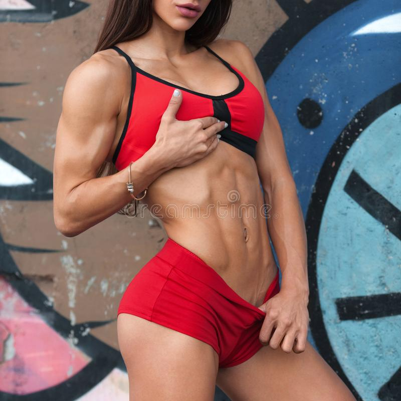 Γυναίκα ικανότητας που παρουσιάζει τα ABS και επίπεδη κοιλιά Αθλητικό κορίτσι υπαίθρια, διαμορφωμένη κοιλιακή, λεπτή μέση στοκ εικόνες