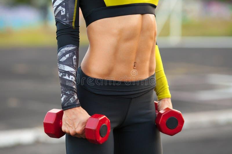 Γυναίκα ικανότητας που παρουσιάζει τα ABS και επίπεδη κοιλιά Μυϊκό κορίτσι με τα dumbbels, διαμορφωμένη κοιλιακή, λεπτή μέση στοκ εικόνα