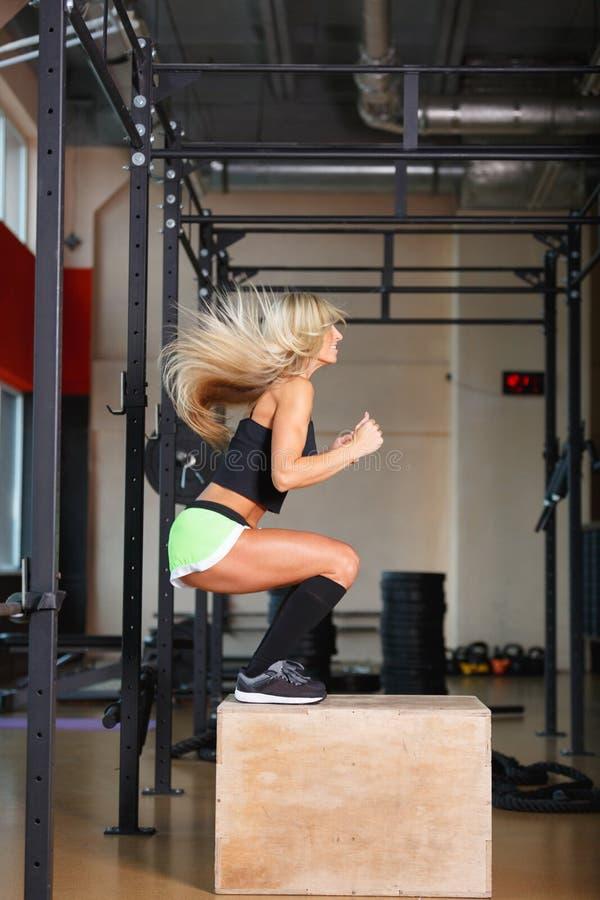 Γυναίκα ικανότητας που πηδά σε ένα ξύλινο κιβώτιο, που ασκεί στη γυμναστική, άποψη από την πλευρά στοκ φωτογραφίες με δικαίωμα ελεύθερης χρήσης