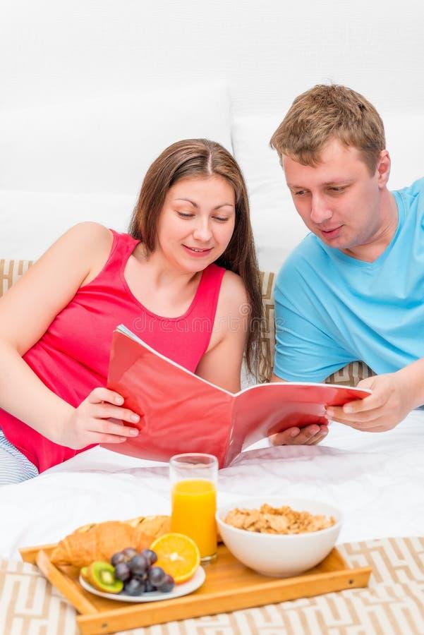 Γυναίκα και άνδρας που φαίνονται ένα περιοδικό στο κρεβάτι στοκ εικόνες με δικαίωμα ελεύθερης χρήσης