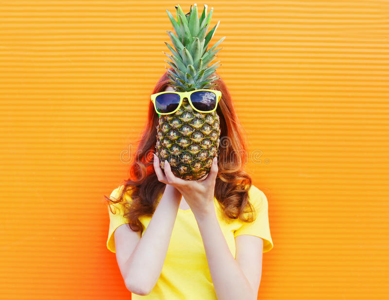 Γυναίκα και ανανάς πορτρέτου μόδας με τα γυαλιά ηλίου πέρα από το ζωηρόχρωμο πορτοκάλι στοκ εικόνες