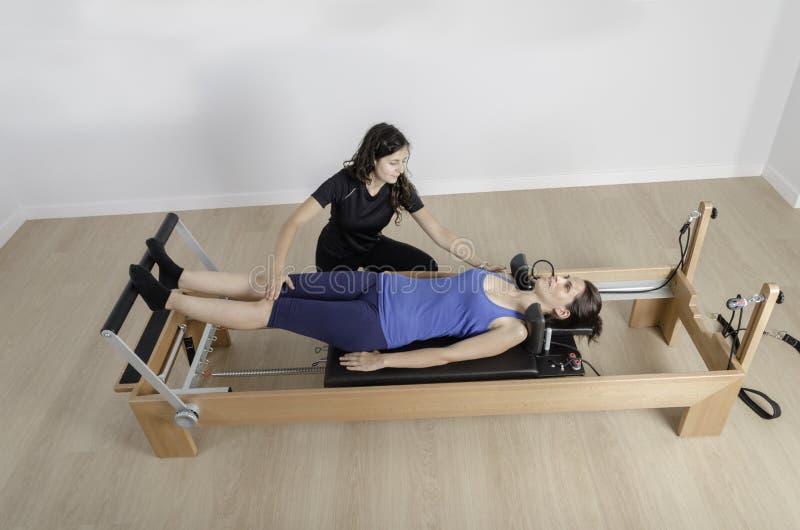 Γυναίκα και εκπαιδευτικός στο κρεβάτι μεταρρυθμιστών, pilates στοκ φωτογραφίες