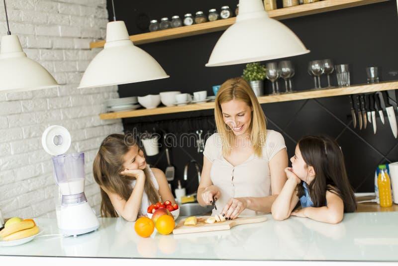Γυναίκα και δύο κορίτσια στην κουζίνα στοκ εικόνα