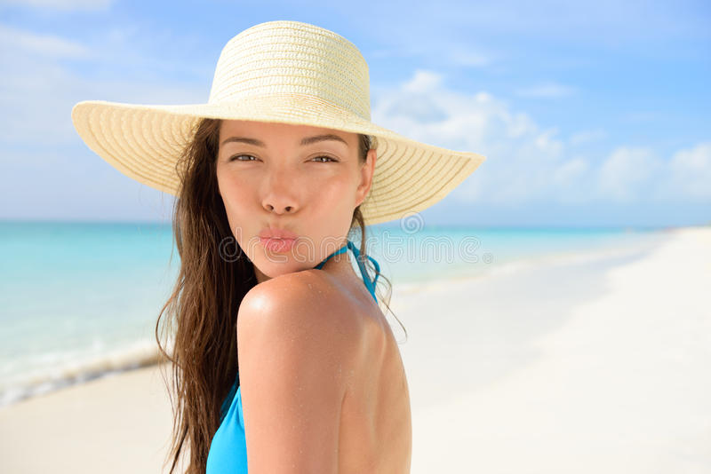 Γυναίκα καπέλων ήλιων παραλιών που φυσά το χαριτωμένο φιλί στις διακοπές στοκ εικόνα