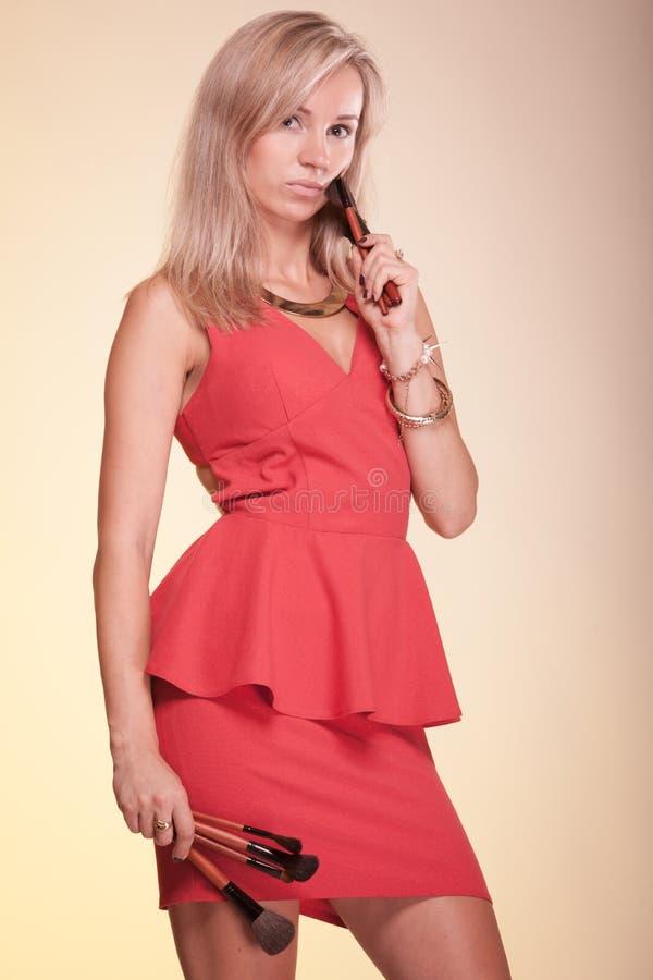 Γυναίκα καλλιτεχνών Makeup στις κόκκινες βούρτσες εκμετάλλευσης φορεμάτων στοκ φωτογραφία