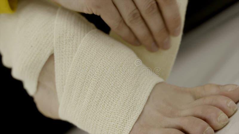 Γυναίκα κινηματογραφήσεων σε πρώτο πλάνο που επιδένει το πόδι της με τον ελαστικό επίδεσμο r Απροσδόκητο ζημία ή τέντωμα του αστρ στοκ εικόνες