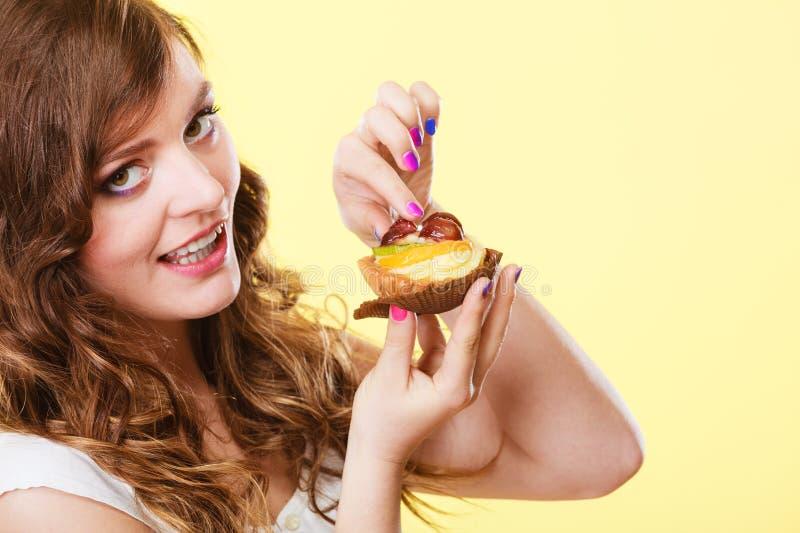 Download Γυναίκα κινηματογραφήσεων σε πρώτο πλάνο που τρώει τα γλυκά τρόφιμα κέικ φρούτων Στοκ Εικόνες - εικόνα από gluttony, κέικ: 62706382