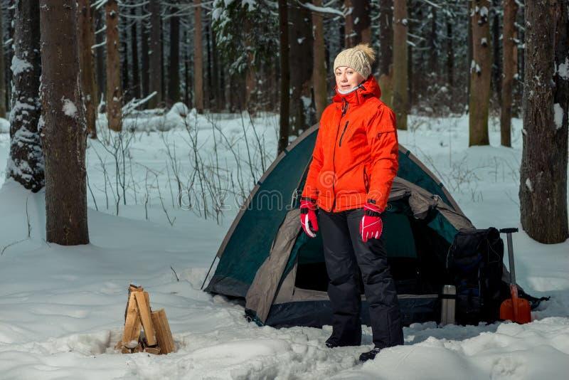 γυναίκα κοντά σε μια σκηνή επί ενός τόπου στρατοπέδευσης σε ένα χειμερινό δάσος στοκ εικόνες με δικαίωμα ελεύθερης χρήσης
