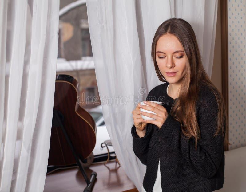 Γυναίκα κοντά στον καφέ κατανάλωσης παραθύρων στοκ εικόνα
