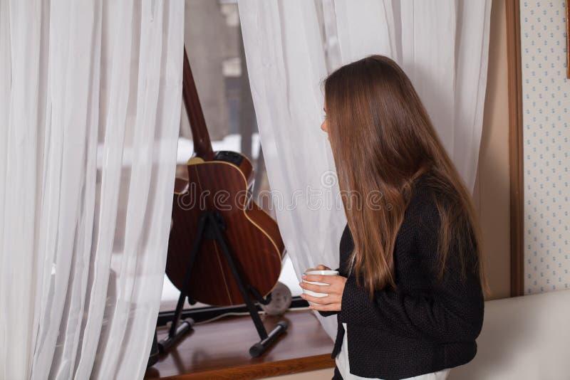 Γυναίκα κοντά στον καφέ κατανάλωσης παραθύρων στοκ εικόνα με δικαίωμα ελεύθερης χρήσης