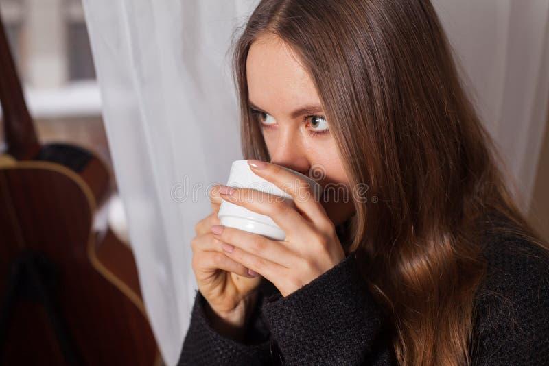 Γυναίκα κοντά στον καφέ κατανάλωσης παραθύρων στοκ φωτογραφίες