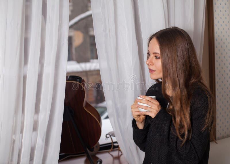 Γυναίκα κοντά στον καφέ κατανάλωσης παραθύρων στοκ φωτογραφία