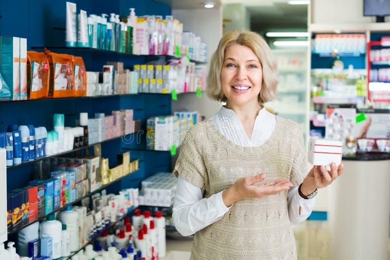Γυναίκα κοντά στο μετρητή στο φαρμακείο στοκ εικόνες