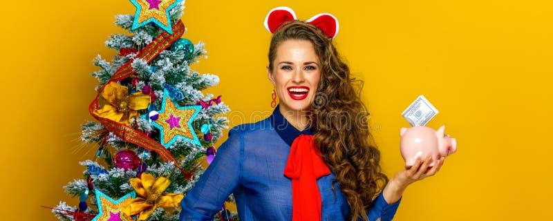 Γυναίκα κοντά στο χριστουγεννιάτικο δέντρο που παρουσιάζει piggy τράπεζα με έναν λογαριασμό δολαρίων στοκ φωτογραφίες