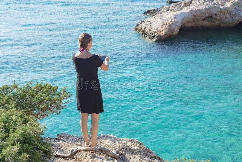 Γυναίκα κοριτσιών καυκάσια στην ωκεάνια άποψη θάλασσας όρμων κόλπων ακτών που παίρνει το τηλέφωνο φωτογραφιών εικόνων στοκ εικόνα