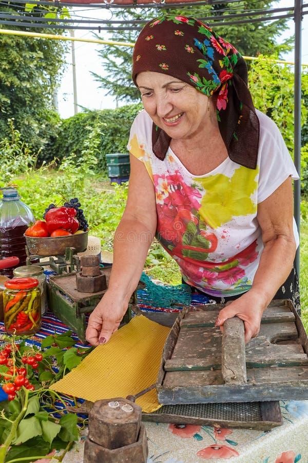 Γυναίκα μελισσοκόμων που παρουσιάζουν κυψέλη κεριών και ηλικιωμένος Τύπος στοκ φωτογραφία με δικαίωμα ελεύθερης χρήσης