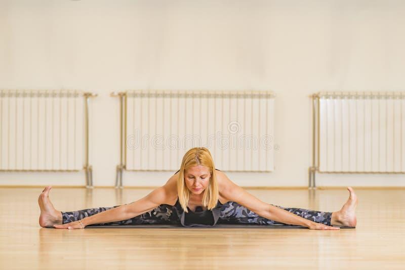 Γυναίκα Μεσαίωνα που κάνει τη γιόγκα σε ένα χαλί άσκησης στο στούντιο στοκ εικόνες