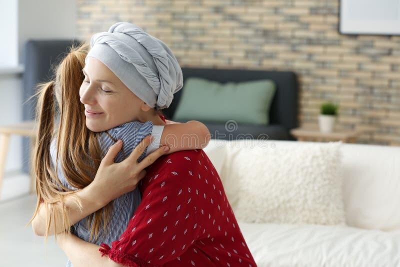 Γυναίκα μετά από τη χημειοθεραπεία που αγκαλιάζει την κόρη της στο σπίτι στοκ φωτογραφία με δικαίωμα ελεύθερης χρήσης