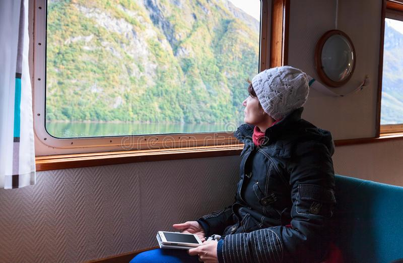 Γυναίκα με ένα κινητό τηλέφωνο που φαίνεται έξω το παράθυρο σε έναν τουρίστα SH στοκ εικόνα