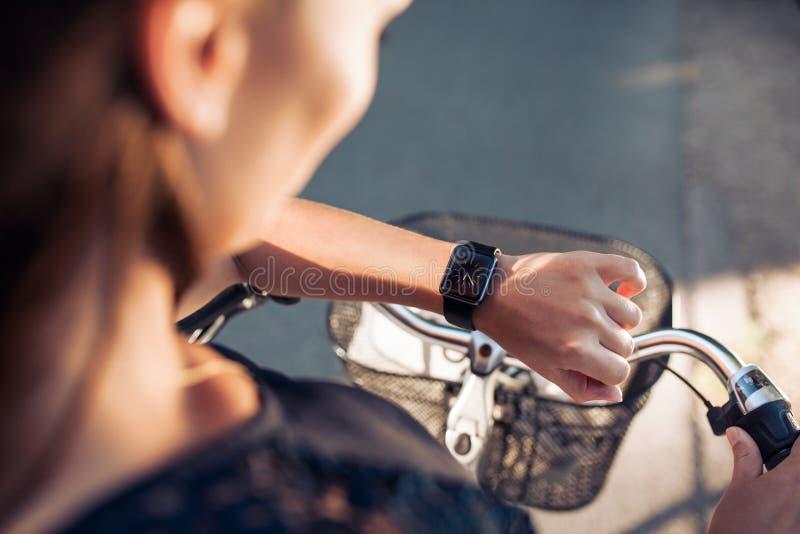 Γυναίκα με ένα ποδήλατο που εξετάζει το smartwatch της στοκ εικόνα