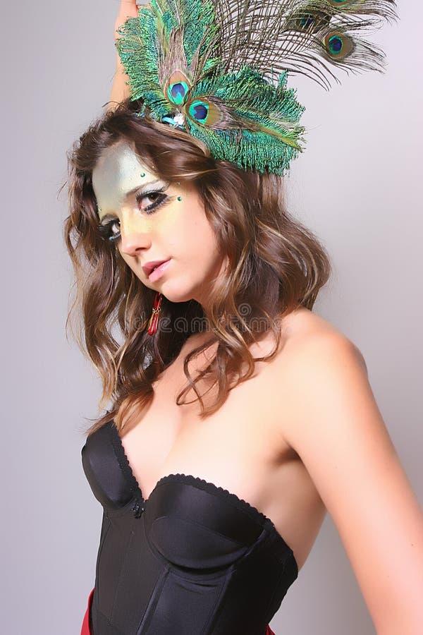 Γυναίκα με ένα φτερό Peacock στην τρίχα της στοκ φωτογραφία