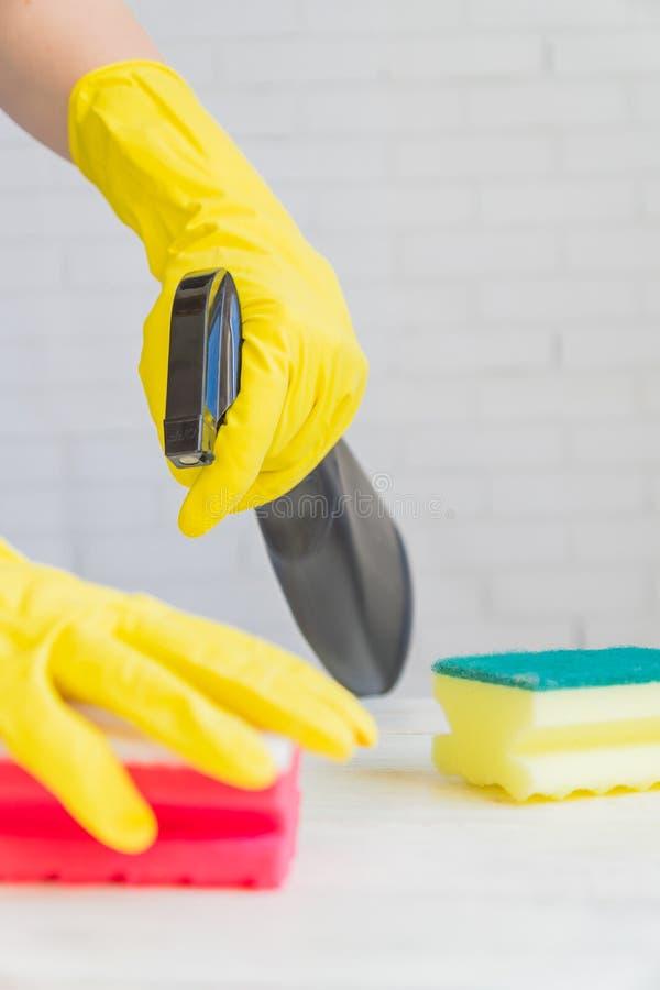Γυναίκα με κίτρινα λαστιχένια γάντια με σπόγγο καθαρισμού. Καθαρισμός  στοκ φωτογραφία