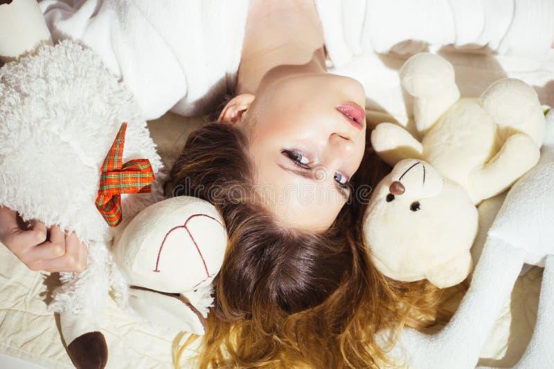 Γυναίκα με μακρυμάλλη στην τρυφερή χαλάρωση πυτζαμών με τη teddy αρκούδα Το κορίτσι με το ήρεμο πρόσωπο βάζει στο κρεβάτι Μαλακή  στοκ εικόνα με δικαίωμα ελεύθερης χρήσης