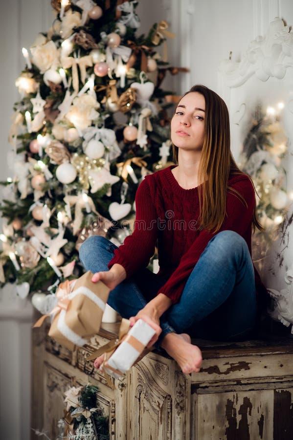 Γυναίκα με μια συνεδρίαση δώρων Χριστουγέννων στο acncient κομό που διακοσμείται για τα Χριστούγεννα Δέντρο του FIR στο υπόβαθρο στοκ φωτογραφίες