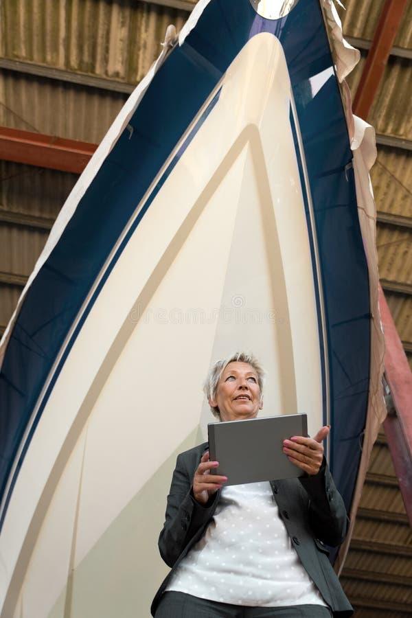 Γυναίκα με μια ταμπλέτα μπροστά από μια βάρκα σε ένα ναυπηγείο στοκ εικόνες