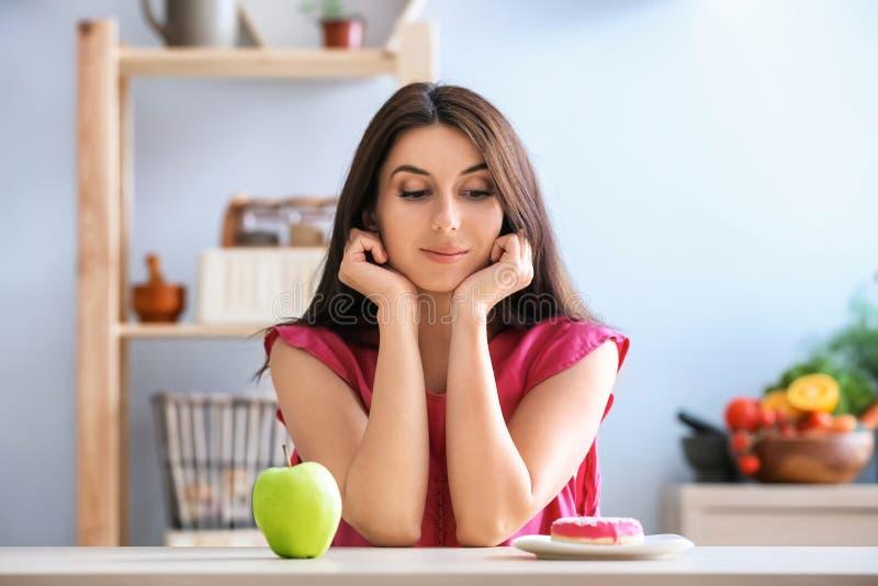 Γυναίκα με νόστιμο doughnut και το φρέσκο μήλο στο εσωτερικό Επιλογή μεταξύ των υγιών και ανθυγειινών τροφίμων στοκ εικόνα