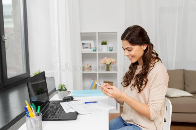 Γυναίκα με τα έγγραφα και smartphone που λειτουργεί στο σπίτι στοκ φωτογραφίες