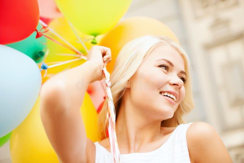 Γυναίκα με τα ζωηρόχρωμα μπαλόνια στοκ φωτογραφία