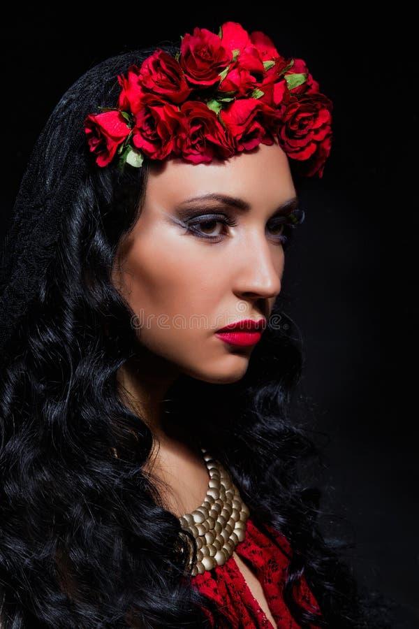 Γυναίκα με τα κόκκινα τριαντάφυλλα στην τρίχα της στοκ εικόνες με δικαίωμα ελεύθερης χρήσης