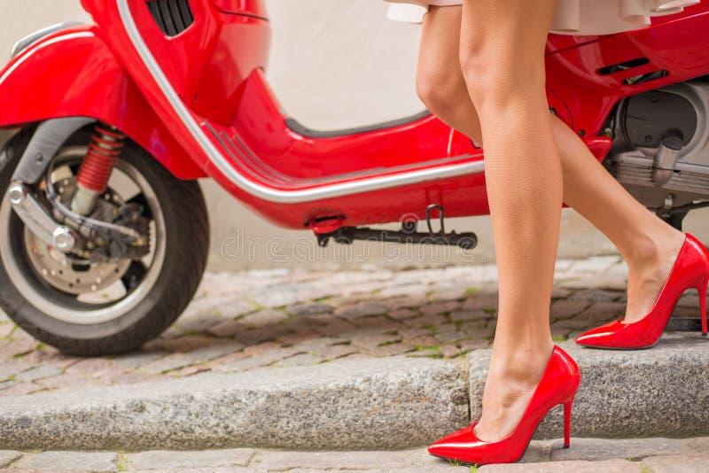 Γυναίκα με τα κόκκινα υψηλά παπούτσια τακουνιών και το κόκκινο λαμπρό μηχανικό δίκυκλο στοκ εικόνες