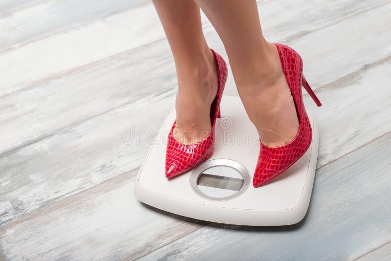 Γυναίκα με τα κόκκινα υψηλά τακούνια στην κλίμακα βάρους στοκ φωτογραφία