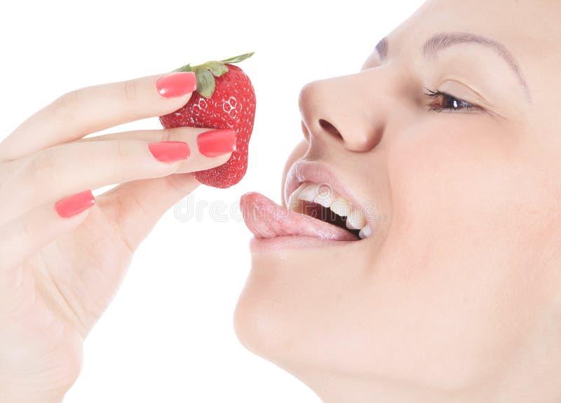 Γυναίκα με τα κόκκινα χείλια που τρώει μια φράουλα στοκ φωτογραφίες με δικαίωμα ελεύθερης χρήσης