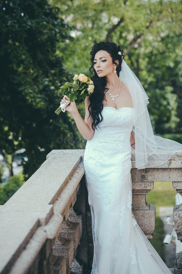 Γυναίκα με τα λουλούδια στο μπαλκόνι Αισθησιακή γυναίκα με τη γαμήλια ανθοδέσμη Κορίτσι ομορφιάς με το νυφικό makeup και hairstyl στοκ εικόνες με δικαίωμα ελεύθερης χρήσης